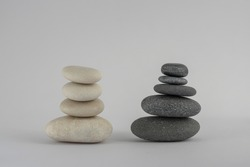 Two simplicity stones cairn isolated on white background, group of four and five black and white pebbles in tower, harmony and balance