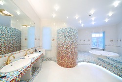 Two sinks and big mirror in spacious bathroom with jacuzzi and blue and red tiles.