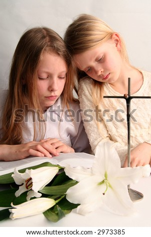 Two sister reading holy bible together and easter lilies lying on the table.