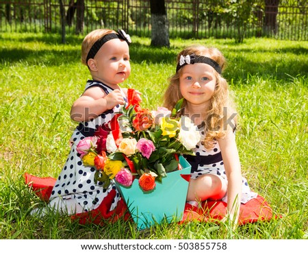 Two sisters. Adorable little child girls with bouquet of flowers on happy birthday. Summer green nature background.