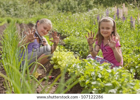 Two sisters (age 7 and 9) has dirty hands from digging in the garden.