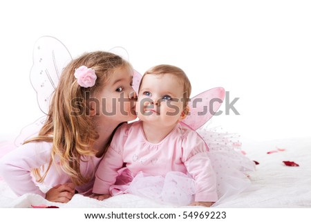 Two sisters are dressed up as fairies.  The older sister is kisssing the baby sister on the cheek.  Horizontal shot.