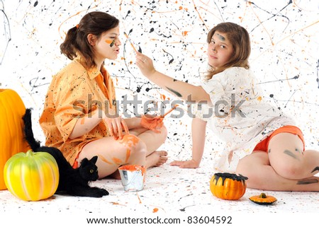 Two sisters deep in black and orange paint, surrounded by pumpkins, a black can and a paint-spattered background.