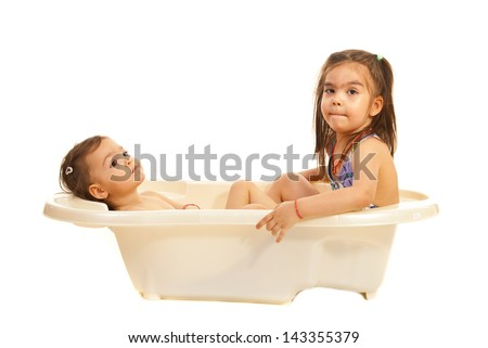 Two sisters dreaming with open eyes in a bath tub isolated on white background