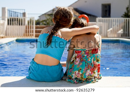 Two sisters embracing each other by the pools edge
