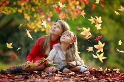 Two sisters girls hugging in a park at autumn day. Kids and fall