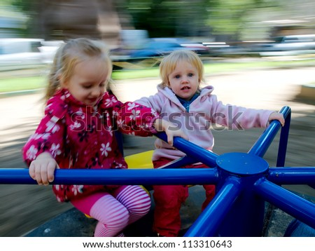 Two sisters having fun on a carousel. Photo with motion blur.