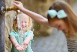 Two sisters having fun with drinking water fountain in Italy on warm and sunny summer day