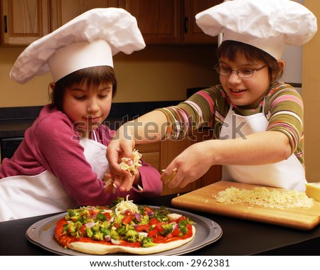 Two sisters in aprons and chef's hats making a veggie pizza.