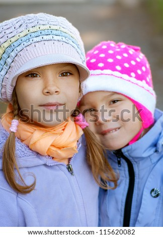 Two sisters-in close-up pre-schoolers in autumn city park.