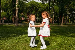 Two sisters jump holding hands, laughing and enjoying nature, children's active outdoor games. The concept of a happy family friendship love