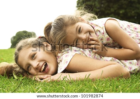 Two sisters laughing and playing in the park, laying down.