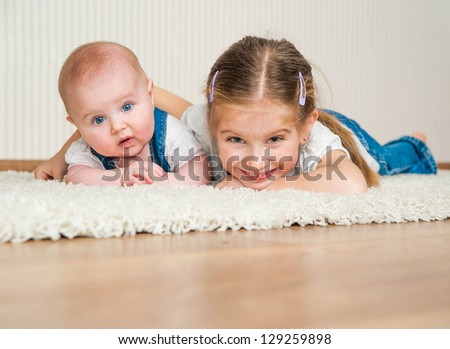 two sisters lying on the floor at home