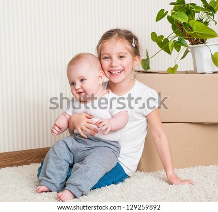two sisters moving into new house, carrying cardboard boxes