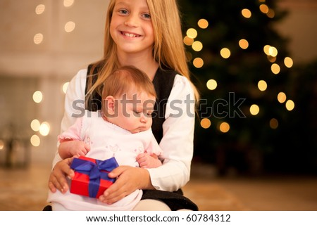 Two sisters - one is still a baby - in front of a Christmas tree with presents