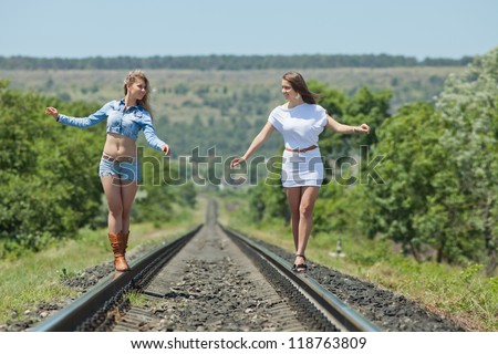 Two sisters outdoors. Two young women are walking along railway