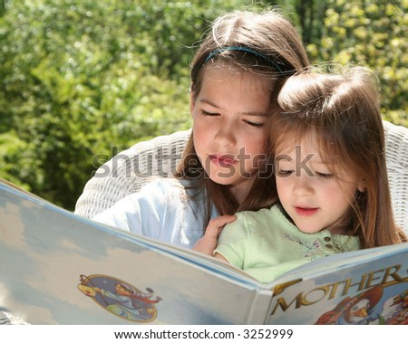 Two sisters outside sharing a book