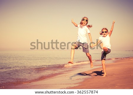 Two sisters playing on the beach at the day time. Concept of friendly sister.