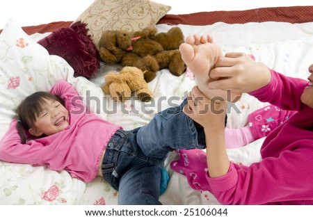 stock-photo-two-sisters-playing-on-the-bed-tickling-feet-25106044.jpg