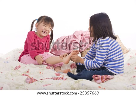 Two sisters playing on the bed, tickling feet. - stock photo