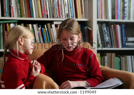 Two sisters reading together - stock photo