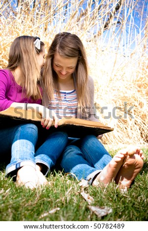Two sisters share a secret together while reading a book.