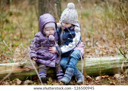 Two sisters sitting on a tree on early spring or late autumn