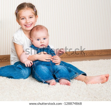 Two sisters sitting on the floor at home