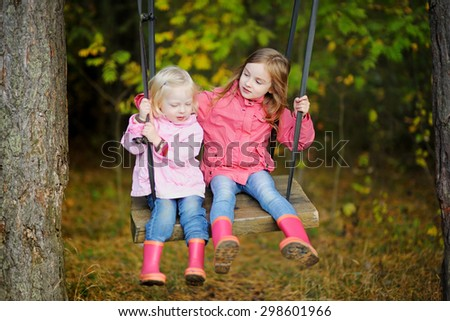 Two sisters swinging outdoors on beautiful sunny autumn day
