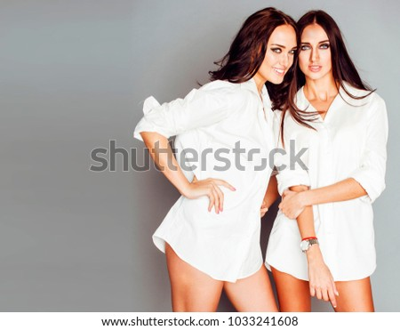 two sisters twins girl posing, making photo selfie, dressed same