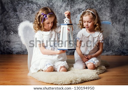 two sisters with angel wings play with flashlight