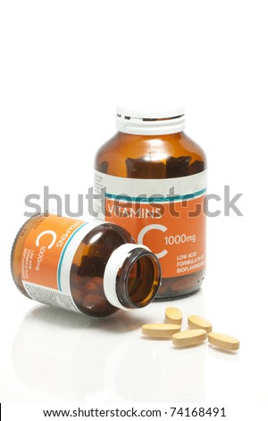 Two size of vitamin C bottle and pill with reflection