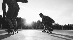 Two skaters friends training outdoor in city park at sunset - Young people skateboarding with longboard in urban contest - Extreme sport concept - Focus on right man legs feet - Vintage vsco filter