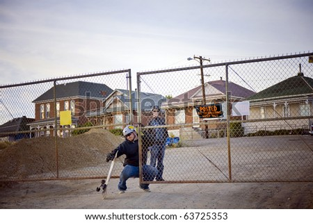 "Two skaters slip through a fence that reads ""No Trespassing"""