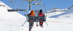 Two skiers go up on chair-lift and snowy ski slope at sun winter day. Caucasus Mountains, Georgia, region Gudauri. Panoramic view.