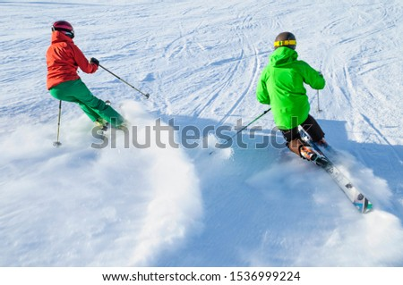 Two skiers having a lot of fun on slope in wintertime #1536999224