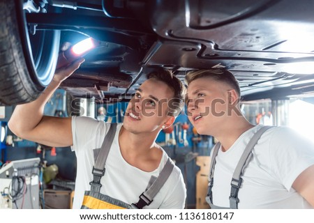 Two skilled auto mechanics analyzing together the rims of a lifted car while working in a modern automobile repair shop