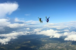 Two skydivers are falling in the amazing sky.
