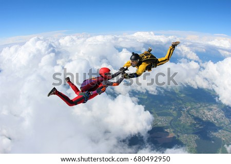 Two skydivers are falling in the background of the white clouds.