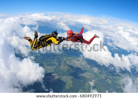 Two skydivers are flying in the sky.