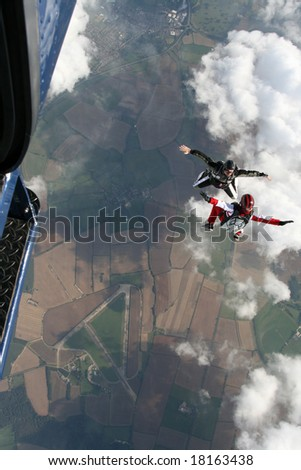 Two skydivers exit a plane in a sit position