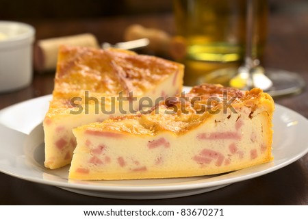 Two slices of cheese and ham quiche with white wine in the back (Selective Focus, Focus on the front surface of the first slice)