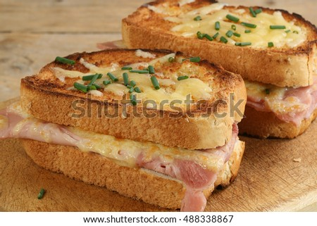 two slices of croque monsieur cheese and ham on a wooden board Photo stock ©