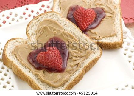 Two slices of honey wheat toast with peanut butter and strawberry jam in a heart shape, topped with a heart shaped strawberry,  selective focus, horizontal closeup with copy space