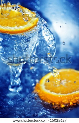 Two slices of orange and a glass in blue clean water
