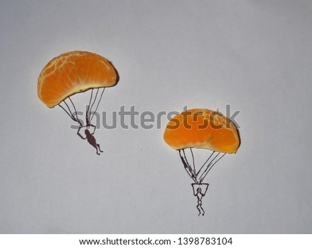 Two slices of orange fruit isolated on grey background like a paratroopers . Imaginative background #1398783104