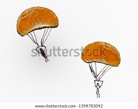 Two slices of orange fruit isolated on white background like a paratroopers . Imaginative background #1398783092