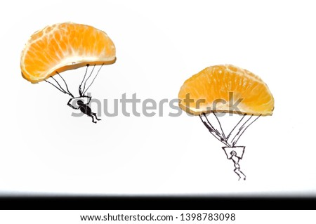 Two slices of orange fruit isolated on white background like a paratroopers . Imaginative background #1398783098