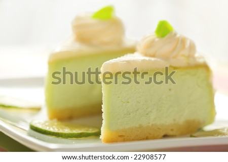 Two slices of silky key lime cheesecake presented with lime slices - stock photo