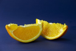Two slices of sweet orange subject photography. Orange still life on dark blue background macro photography. Juicy citrus fruit close-up photography.